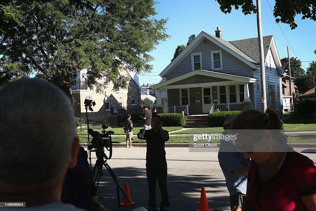 News crews report from outside the home of Wade Michael Page August 6, 2012 Cudahy, Wisconsin. Page is reported to have opened fire at the Sikh Temple of Wisconsin killing six people before being killed by police during a shootout.
