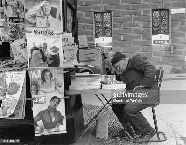 A news dealer sleeping outside his stand Milan 1950s