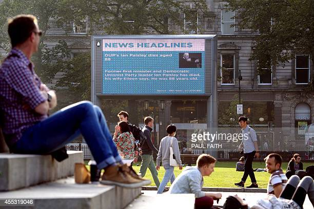 A news feed on a big screen in the grounds of Belfast City Hall displays an announcement of the death of former Nothern Ireland first minister Ian...