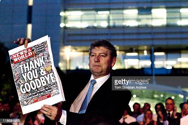 News of The World Editor Colin Myler holds the front page of the last edition of the paper as he leads staff and journalists out of the Thomas More...