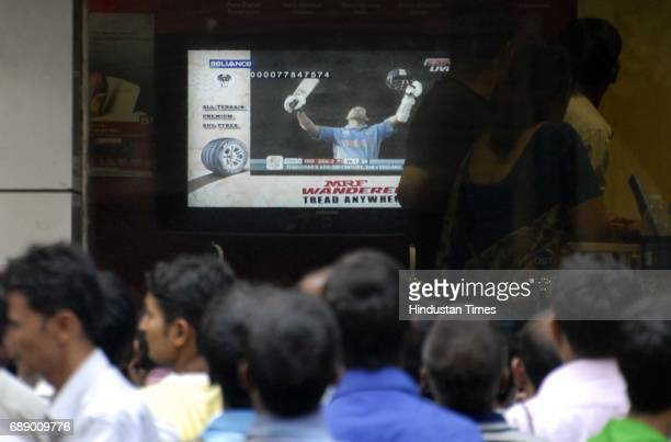 News People watch Sachin Tendulkar after scoring a century at IndiaEngland World Cup Match outside an electronic store at Mahim