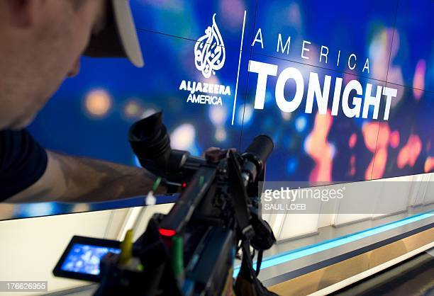 A news photographer films the logo of the new Al Jazeera America nightly news program America Tonight in the network's studio space at the Newseum in...