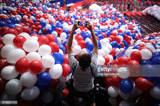 A news photographer makes images of nets filled with thousands of red white and blue balloons before they are lifted into the ceiling of the Quicken...