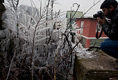 A news photographer take pictures of tree branches covered in icicles during a cold day on December 31 2014 in Srinagar the summer capital of Indian...