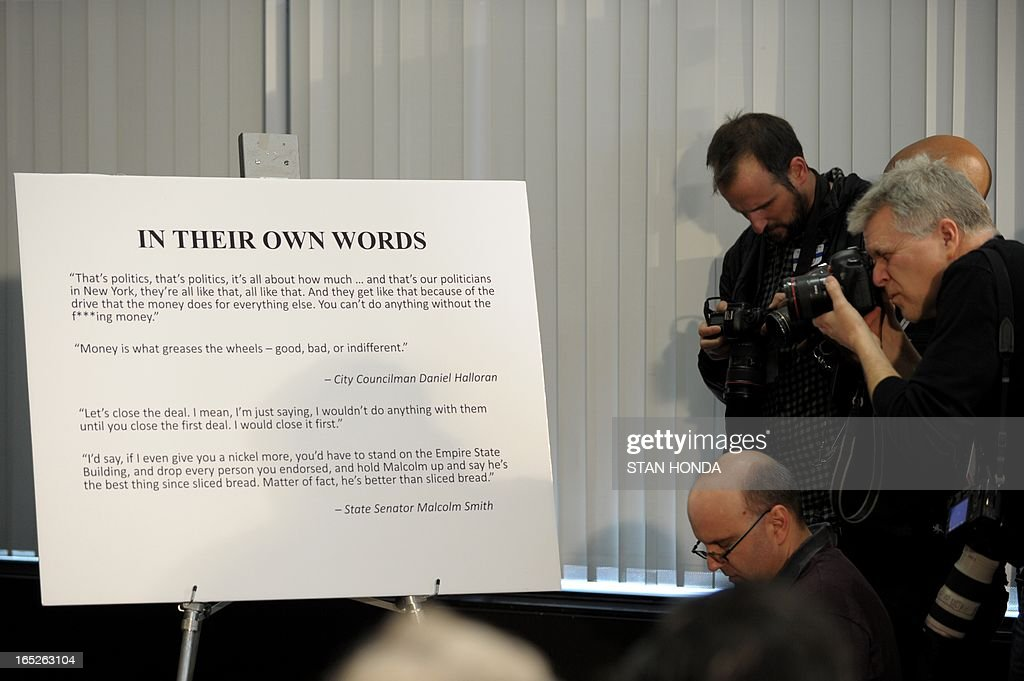 News photographers take pictues of a chart with quotes from defendants as Preet Bharara, United States Attorney for the Southern District of New York, announces federal corruption charges againt New York State Senator Malcolm Smith and New York City Council member Daniel Halloran at a press conference April 2, 2013 in New York. The FBI says Smith and City Councilman Dan Halloran were arrested early Tuesday at their homes for allegedly plotting to rig the New York City mayor's race. Bharara said in a statement that Smith 'tried to bribe his way' into a shot at the New York City mayoral race. AFP PHOTO/Stan HONDA