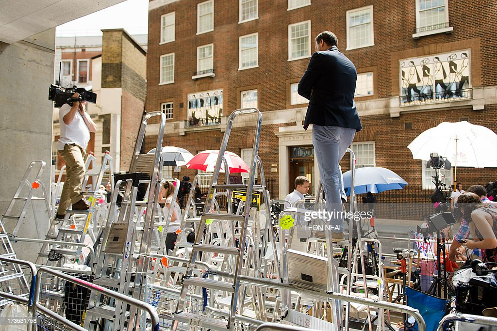 A news reporter (R) does a piece to a television camera while standing on a ladder outside the Lindo Wing of Saint Mary's Hospital in London, on July 16, 2013, where Prince William and his wife Catherine's baby is expected to be born. Britain's Prince Charles joked Monday that his son Prince William's baby was 'hopefully' on the way, but wife Camilla went further, saying it could arrive 'by the end of the week'.