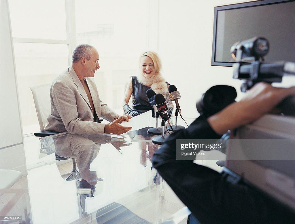 News Reporter Interviewing A Female Pop Musician Sitting