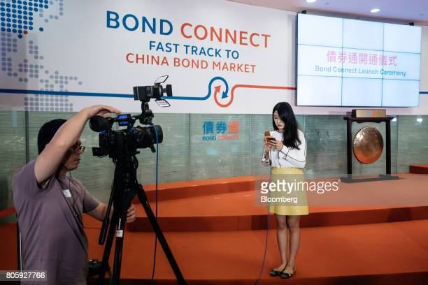 A news reporter prepares to speak to a television camera in front of signage for the ChinaHong Kong Bond Connect at the Hong Kong Stock Exchange in...