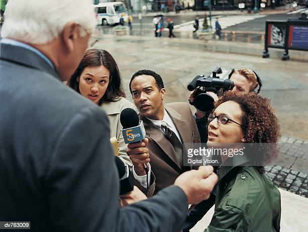 News Reporters and a TV Cameraman Interviewing a Mature Man in the City