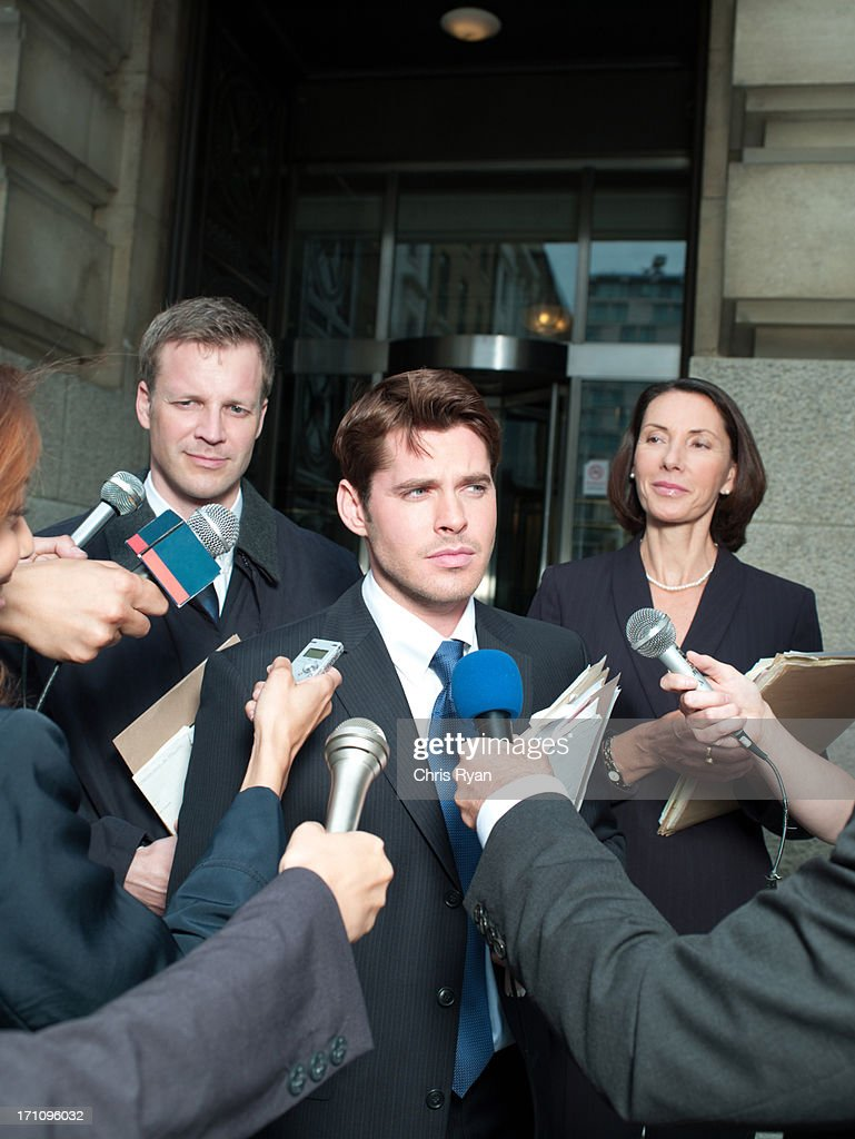 News reporters interviewing smiling man outside courthouse : Stock Photo
