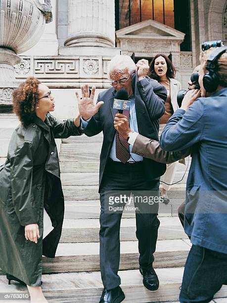 News Reporters Trying to Interview a Mature Man in a Suit on the Steps of a Building