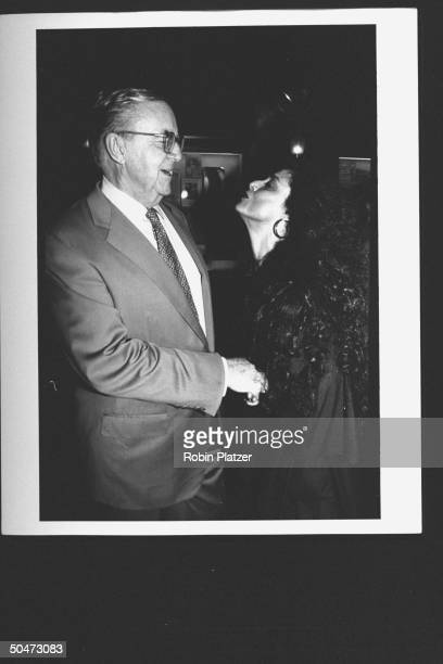 TV news show host John McLaughlin in handholding faceoff w actress Sonia Braga who is puckered up to give him a kiss at premiere party for the movie...
