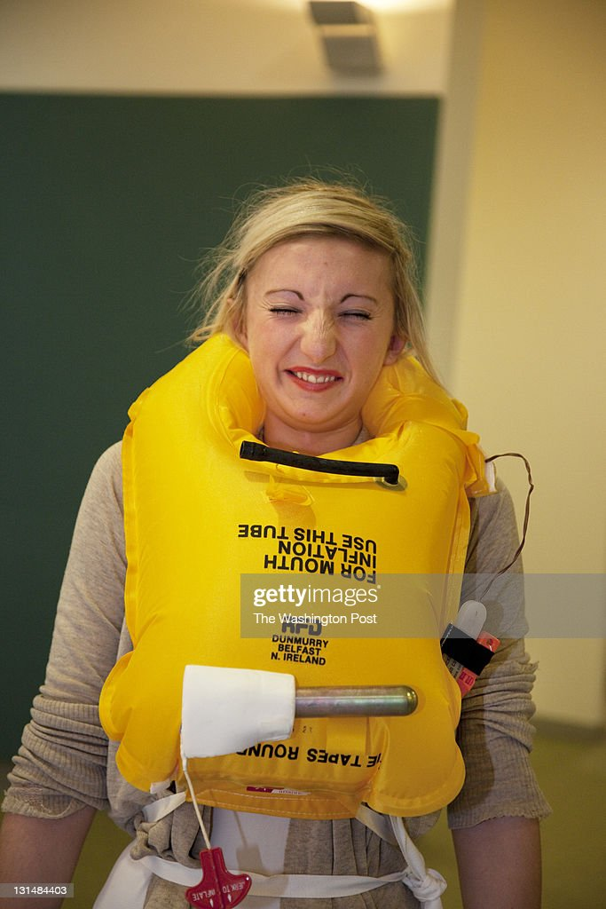 SUSSEX, UK, OCTOBER 27TH 2011. News student recruits fire off the gas to inflate their safety equipment during life jacket training. Virgin Atlantic air stewardess and steward training at The Base training facility.