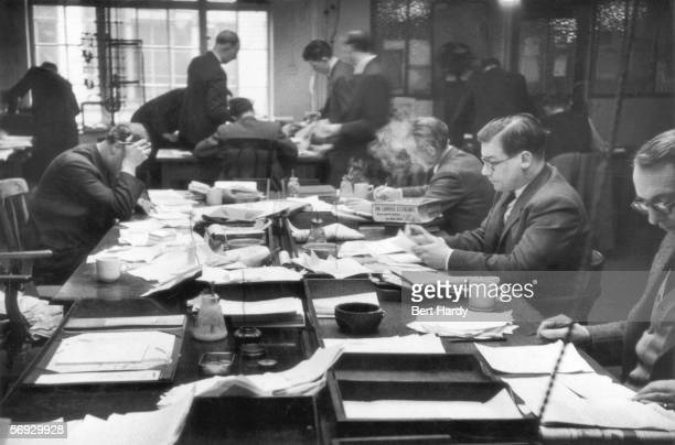 News subs work on the constant influx of copy in the newsroom of the News of the World newspaper on Fleet Street 18th April 1953 Original Publication...
