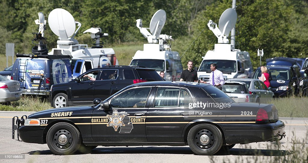 News trucks gather at the location where FBI agents are searching a field for the remains of former Teamsters' union president Jimmy Hoffa June 17, 2013 in Oakland Township, Michigan. The agents were acting on a tip provided by Tony Zerilli, 85, a former mobster, who was released from prison in 2008. Hoffa, who had reported ties to organized crime, went missing in July of 1975.