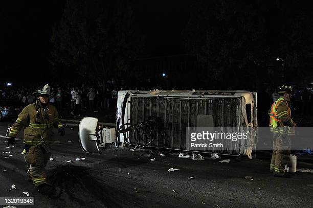 A news van is flipped over as students and those in the community fill the streets and react after football head coach Joe Paterno was fired during...