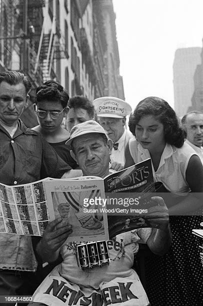 A news vendor looks through the premiere issue of Sports Illustrated magazine on a Manhattan sidewalk as onlookers read over his shoulder New York...