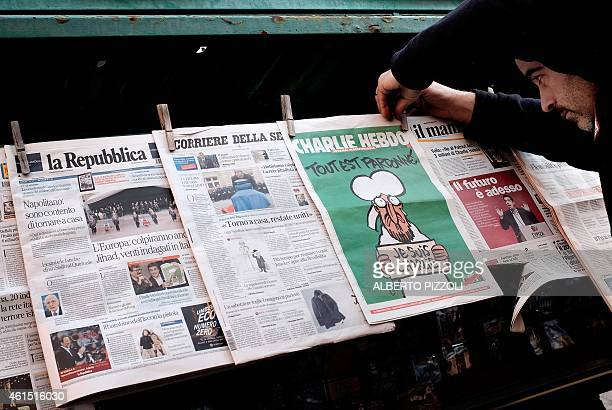 A newsagent displays the latest edition of French satirical magazine Charlie Hebdo at his kiosk in Rome on January 14 2015 The latest issue of...