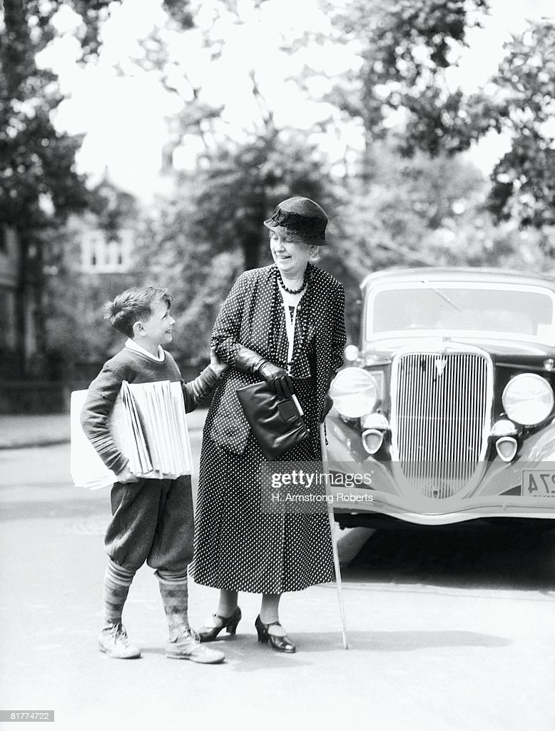 Newsboy with stack of papers under arms, helping elderly woman with cane cross street. : Stock Photo