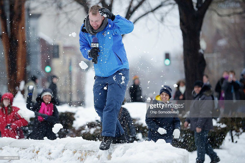 NewsChannel 8's Mike Conneen is pelted with snowballs as he trys to report from Dupont Circle February 13, 2014 in Washington, DC. Up to 12 inches of snow fell over the Washington area causing WMATA to cancel bus service but rail service continued to operate.