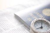 A newspaper, a passport, and a world clock