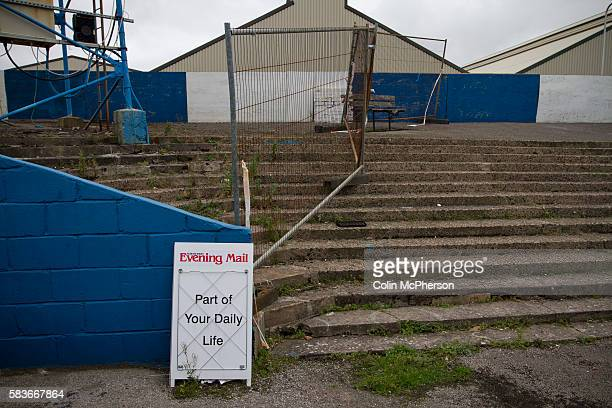 A newspaper advert in front of a disused section of the terracing at Barrow AFC's Furness Building Society Stadium during the Barrow v Newport County...