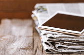 Newspaper and digital tablet on wooden table