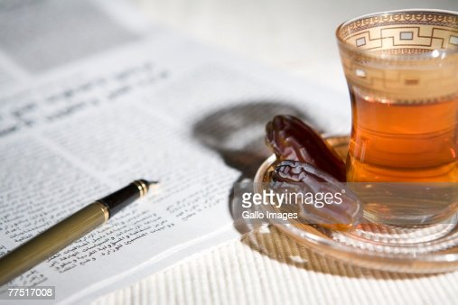 Newspaper and Pen Beside Arabic Tea and Dates. Dubai, United Arab Emirates