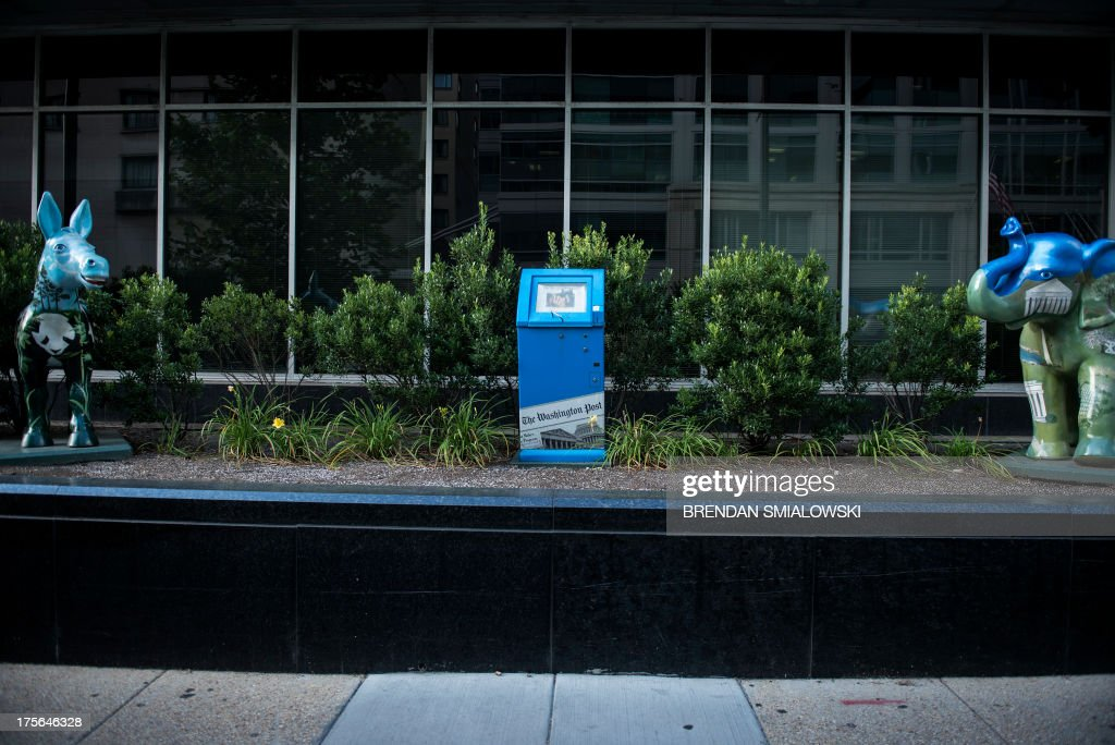 A newspaper box is seen outside The Washington Post on August 5, 2013 in Washington, DC after it was announced that Amazon.com founder and CEO Jeff Bezos had agreed to purchase the Post for USD 250 million. Multi-billionaire Bezos, who created Amazon, which has soared in a few years to a dominant position in online retailing, said he was buying the Post in his personal capacity and hoped to shepherd it through the evolution away from traditional newsprint. AFP PHOTO/Brendan SMIALOWSKI