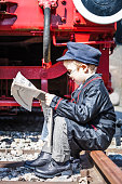 Small child boy as nostalgic locomotive driver sitting at the railway track and reading a newspaper at lunch hour