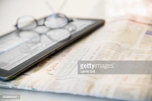 Newspaper, eyeglasses and digital tablet