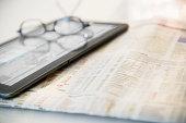 Newspaper, eyeglasses and digital tablet
