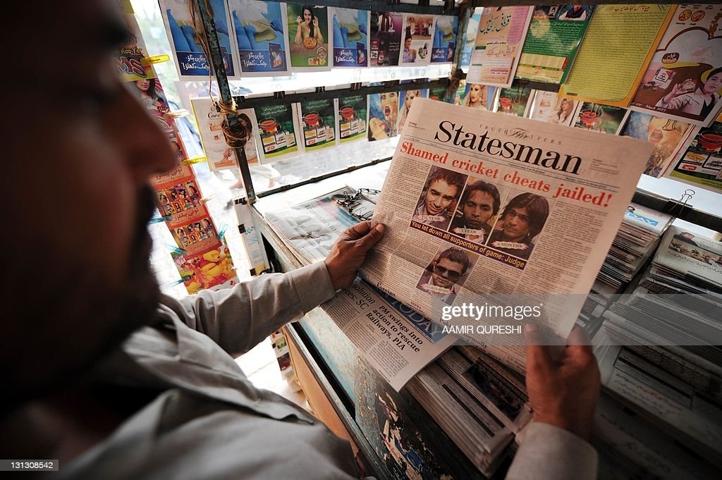 A newspaper front page featuring coverage of Pakistani cricketers jailed in the UK over matchfixing is displayed at a roadside stall in Islamabad on...