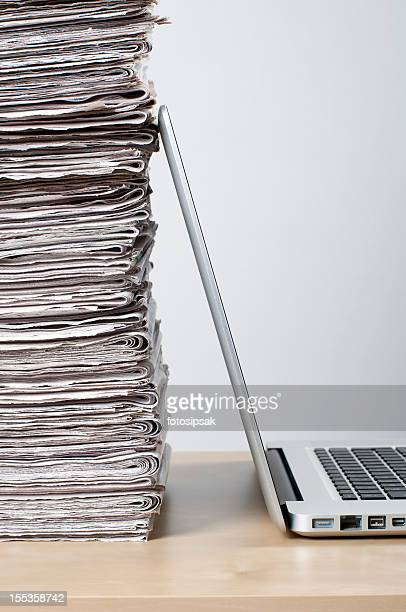 Newspaper pile and laptop depicting online news concept