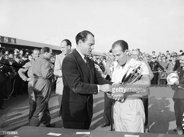 Newspaper publisher Max Aitken presenting Stirling Moss with his cup for winning the Daily Express International Trophy at the Silverstone circuit in...