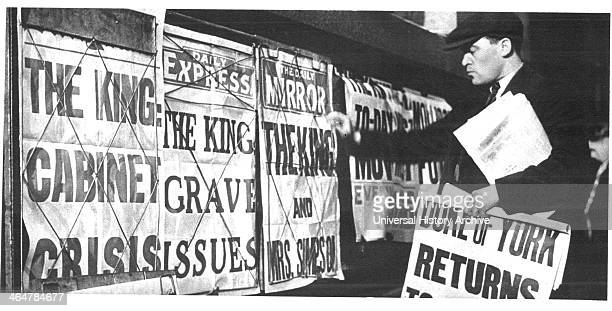 Newspaper seller adjusting his headline posters during the Edward VIII abdication crisis of 1937