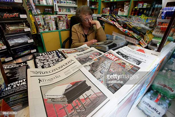 A newspaper seller sits by Monday editions of Polish newspapers all bearing news concerning the death of Polish President Lech Kaczynski on April 12...