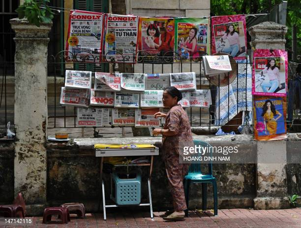A newspaper vendor arranges her stand set up on the fence of a villa in downtown Hanoi on June 26 2012 Vietnamese Minister of Information and...