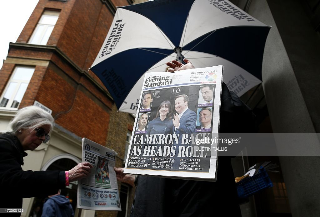 A newspaper vendor gives out free newspapers showing election victory for British Prime Minister David Cameron's Conservative Party at a news stand...