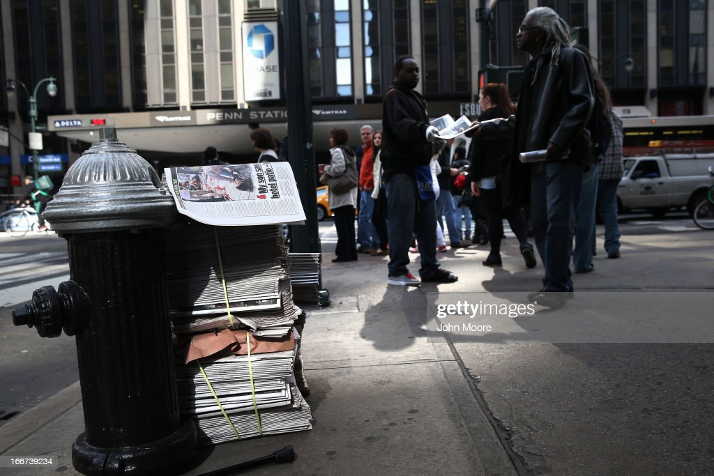 A newspaper vendor hands out free copies of The New York Daily News ouside of Penn Station on April 16, 2013 in New York City. Police were out in force throughout New York, a day after explosions near the finish line of the Boston Marathon killed 3 people and wounded more than 170 others.