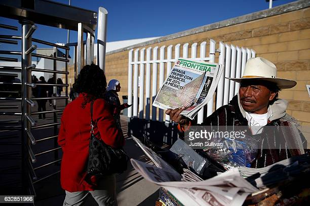 A newspaper vendor holds a newspaper with a front page story about US President Donald Trump's proposed tax on Mexico to pay for a border wall near...