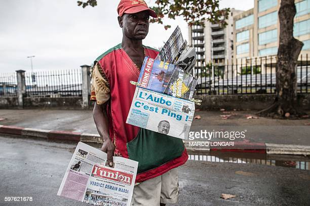 A newspaper vendor looks for customers at a street light in Libreville on August 29 2016 while displaying local papers reporting on the outcome of...