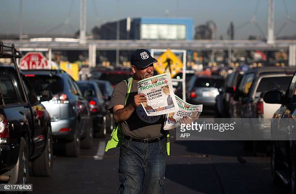 A newspaper vendor sells local newspapers highlighting the US Presidential Election on their front pages at San Ysidro Crossing Port in Tijuana...