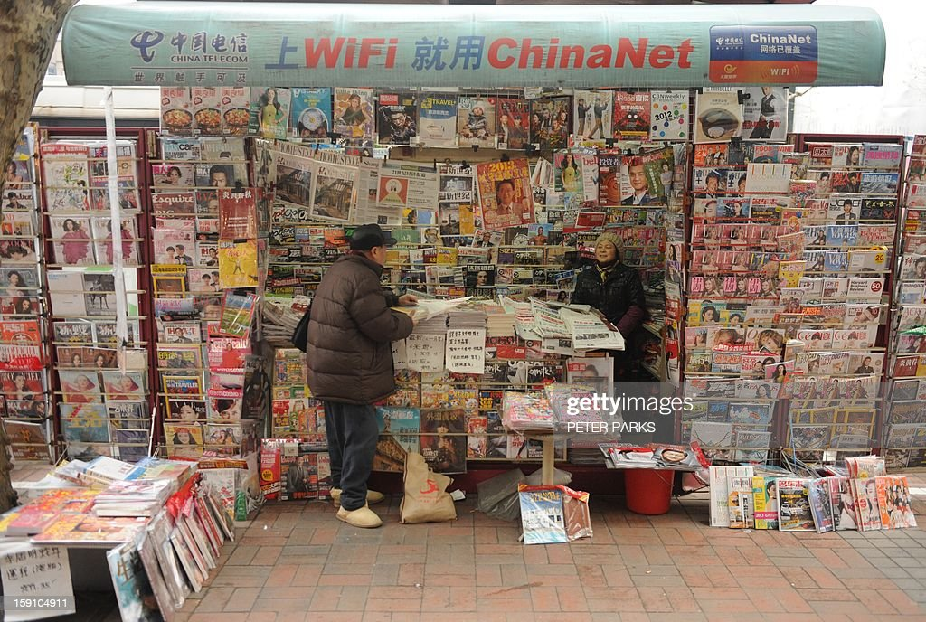 A newspaper vendor (R) talks to a customer at her booth on a street in Shanghai on January 8, 2013. China's blogosphere and celebrities, many with millions of followers, backed journalists at the Southern Weekly, a popular liberal newspaper based in Guangzhou which is embroiled in a censorship row after hundreds of people held a rare protest demanding greater press freedom after an article urging reforms to uphold people's rights was censored by an official. AFP PHOTO/Peter PARKS
