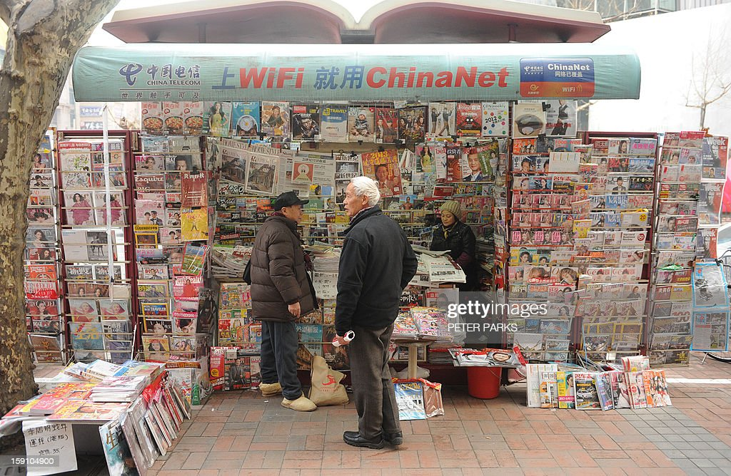 A newspaper vendor (R) talks to customers at her booth on a street in Shanghai on January 8, 2013. China's blogosphere and celebrities, many with millions of followers, backed journalists at the Southern Weekly, a popular liberal newspaper based in Guangzhou which is embroiled in a censorship row after hundreds of people held a rare protest demanding greater press freedom after an article urging reforms to uphold people's rights was censored by an official. AFP PHOTO/Peter PARKS