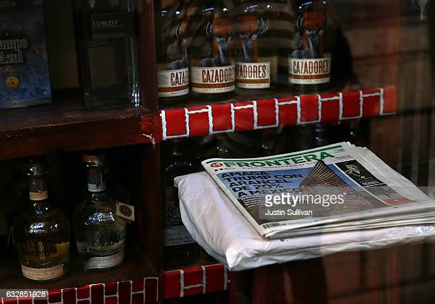 A newspaper with a front page story about US President Donald Trump's proposed tax on Mexico to pay for a border wall sits next to bottles of tequila...