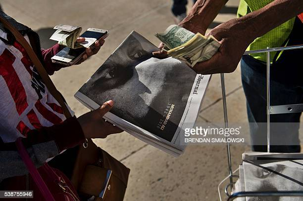 A newspaper with Muhammad Ali is sold after people waited in line for tickets to a memorial service outside the KFC Yum Center for the boxing legend...