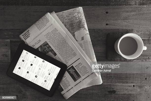 Newspapers and digital tablet displaying the news with morning coffee on a rustic wooden table