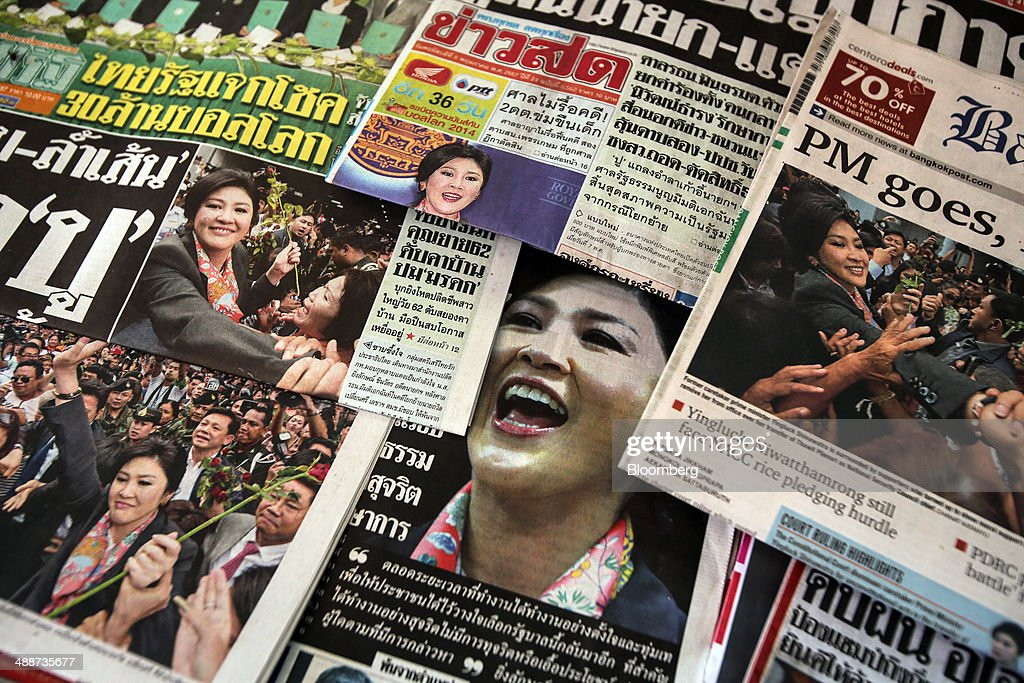Newspapers featuring ousted Prime Minister Yingluck Shinawatra on their front pages are arranged for a photograph at a newsstand in Bangkok, Thailand, on Thursday, May 8, 2014. The baht fell to a one-month low and stocks slumped on concern global investors will shun Thailand after a court ruling to remove Yingluck Shinawatra as prime minister worsened the nation's political crisis. Photographer: Dario Pignatelli/Bloomberg via Getty Images
