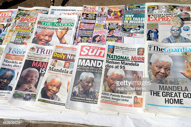 Newspapers front pages bearing portraits of late President Nelson Mandela are displayed at a newsstand in Lagos on December 6 2013 Very few people...